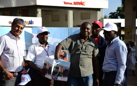 "Tushar Mashru (2nd L), Total Uganda dealer, Richard Jjuko, (C) Total Wampewo Station Manager, with a customer picking a raffle ticket during the Total Uganda ""Extra Mile"" promotion on 2nd November 2018 at Total Wampeewo station. Lucky Winners of the draw will get free full-year car service."