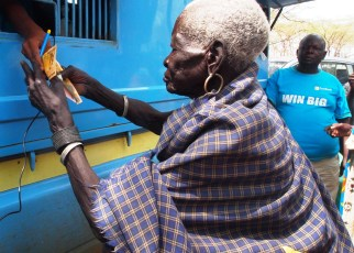 Teko Okudo recieving money from the mobile bank van in Moroto