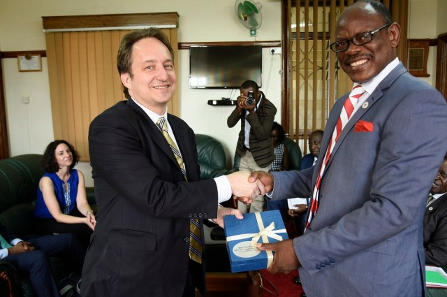 Yale University's Vice President, Pericles Smith (L) hands over a present to Makerere University Vice Chancellor Prof. Barnabas Nawangwe at Makerere University during an official visit in Uganda on March 13, 2019. This was during the Yale's stuff visit to meet the university Alumni and partners