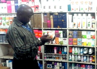 Uganda National Bureau of Standards official checks suspected substandard cosmetics in a shop in Kampala