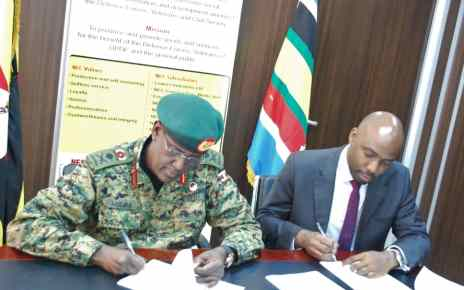 Managing Director of NEC, Lt Gen. James Mugira, (Left) and Executive Director of UFZA Richard Jabo (Right) pens down the deal at NEC offices in Bugolobi, Kampala recently