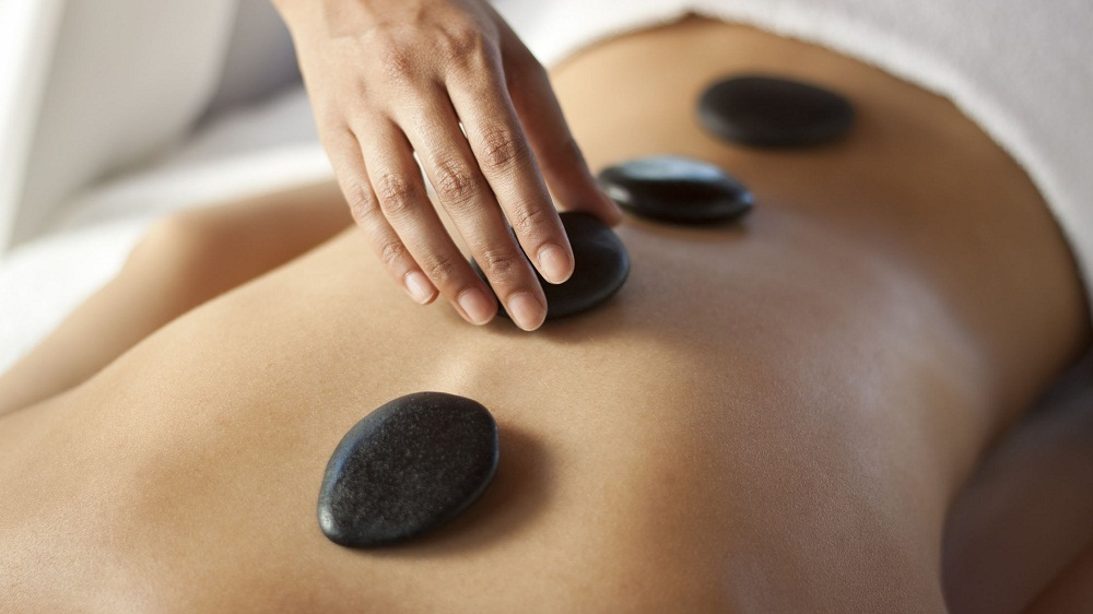 A hot stone massage is a type of massage therapy. It's used to help you relax and ease tense muscles and damaged soft tissues throughout your body.