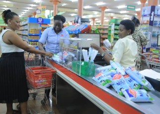 Allen Mwigarire Ssejemba (L), a customer of Fresh Dairy shops an assortment of Fresh Dairy products at Capital Shoppers, while Hajara Logose, Sales Fresh Dairy (C ) looks on. Consuming 3 dairies a day ensures that families maintain a healthy balanced diet.
