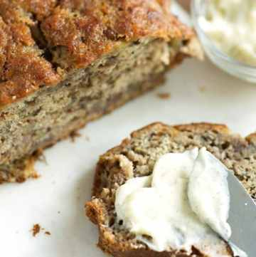 A slice of browned butter banana bread with vanilla butter