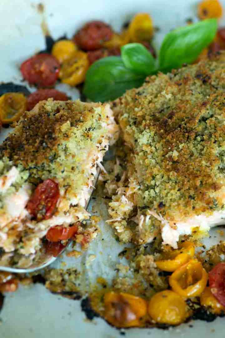 Salmon with herbed butter on a baking sheet with a serving fork