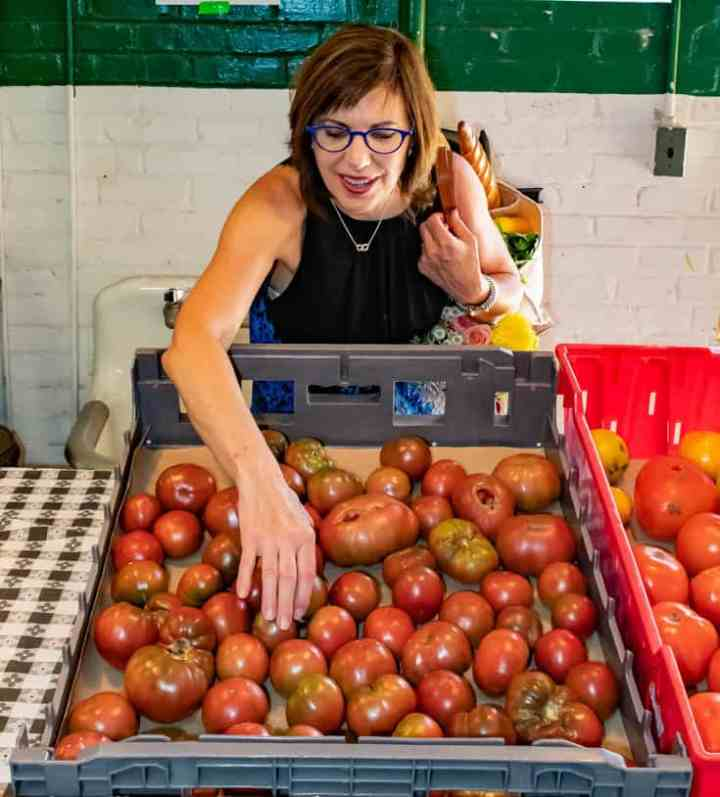 Barbara choosing a tomato at the farmers market