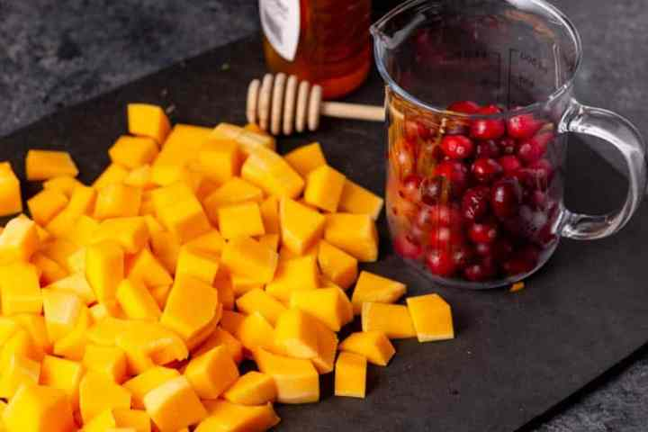 A cutting board with cubed butternut squash and a beaker of fresh cranberries