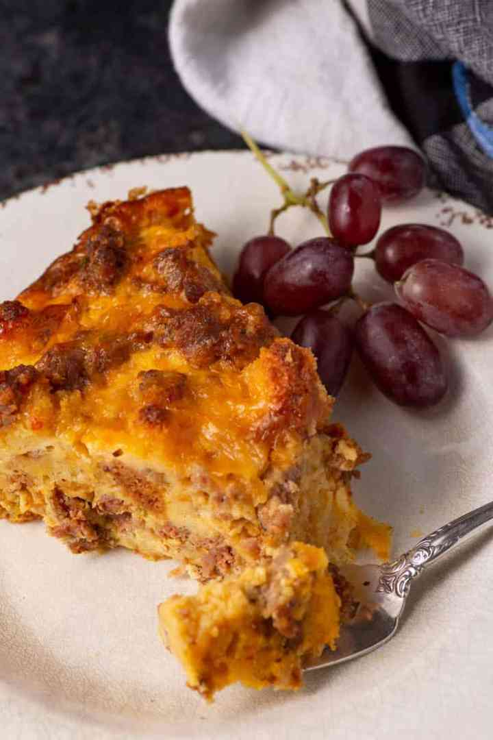 A slice of cornbread and sausage Quiche with grapes on a plate