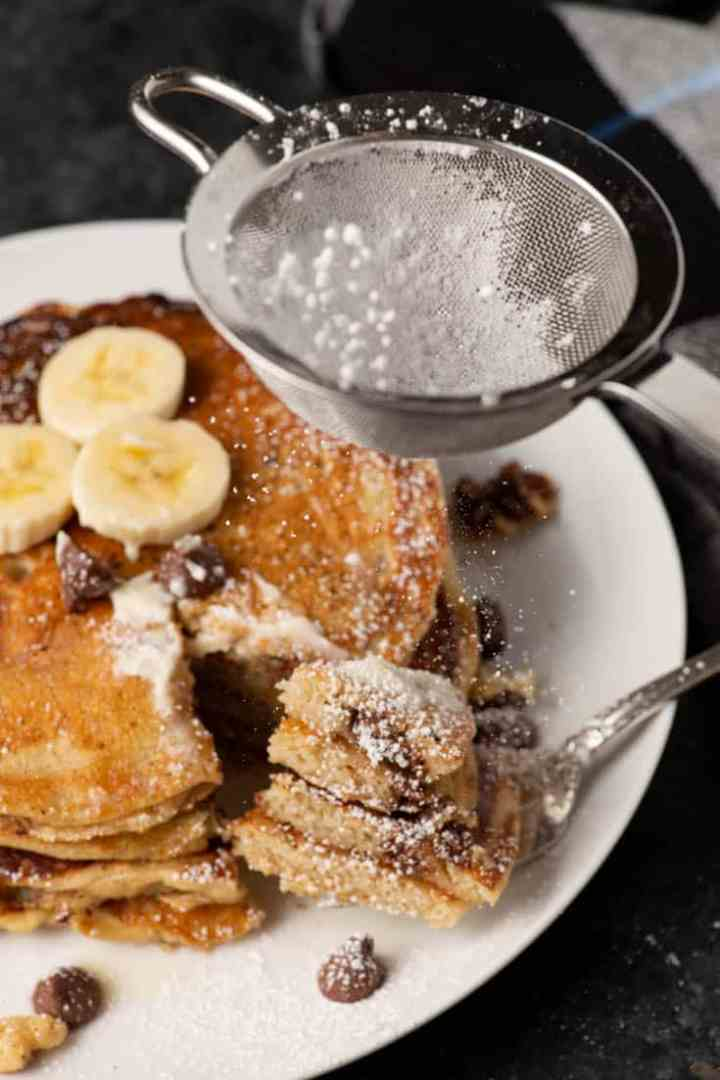 Powdered sugar being sprinkles over banana bread pancakes