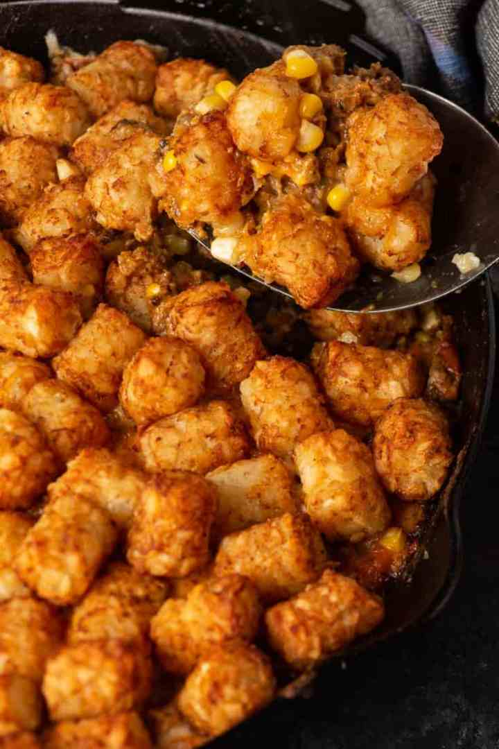 A scoop of tater tot casserole on a spoon