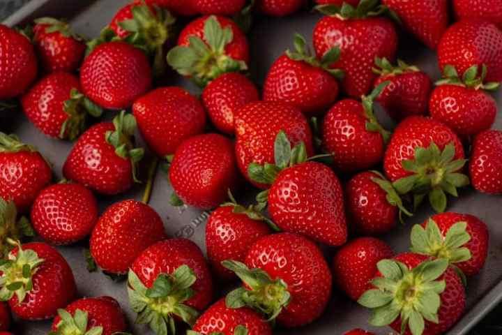 A rimmed baking sheet full of fresh strawberries