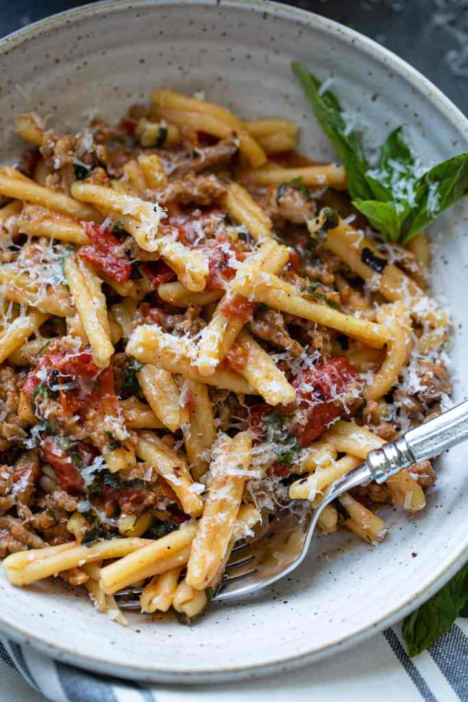 pasta noodles with fire roasted tomatoes and basil with fork