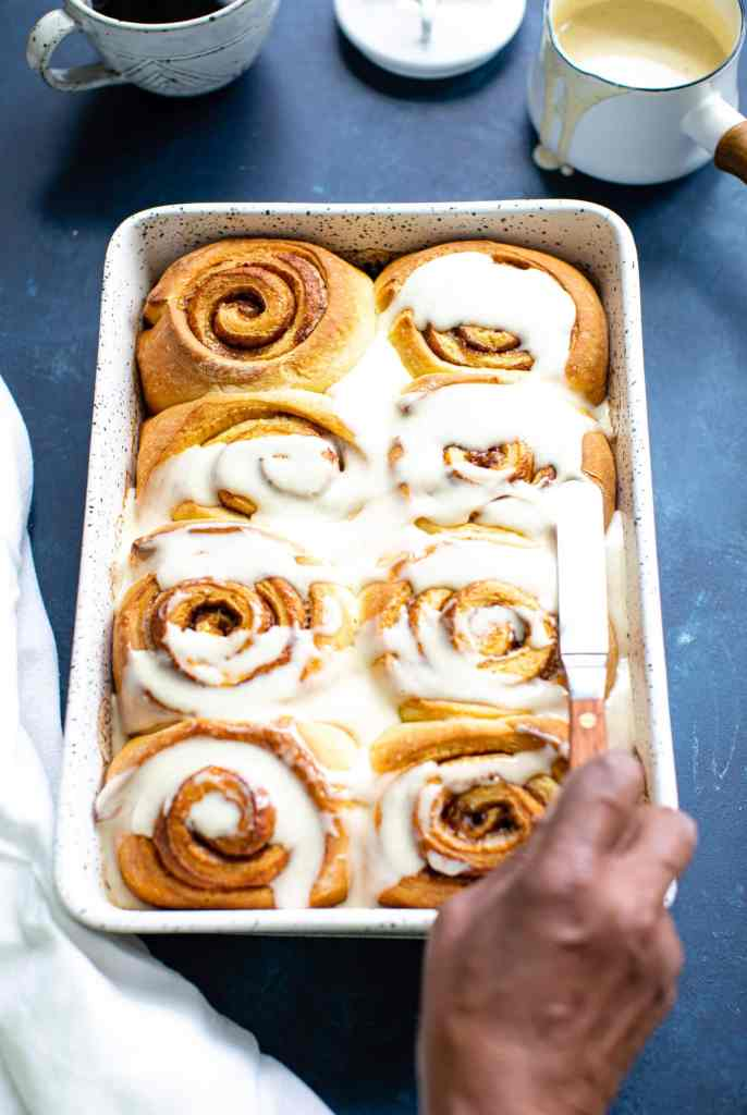 black woman's hand frosting cinnamon rolls in a baking dish