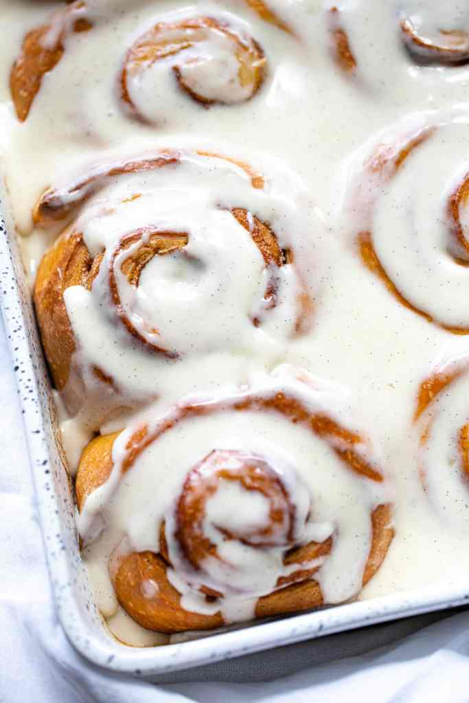 close up shot of cinnamon rolls in baking dish with frosting