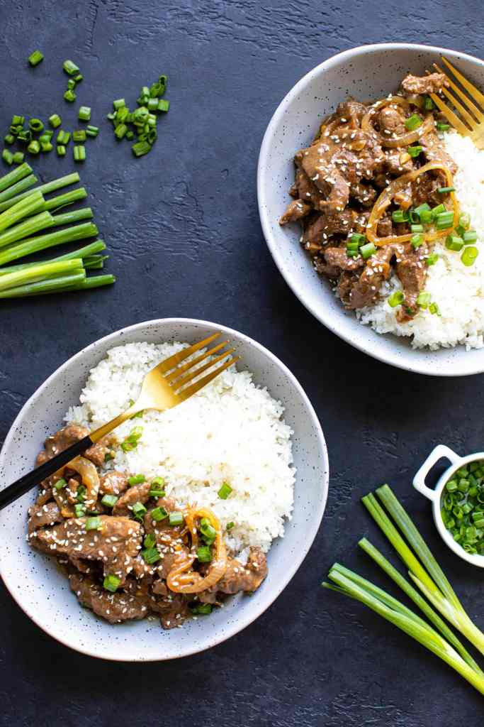 two gray specked bowls with beef and rice with forks