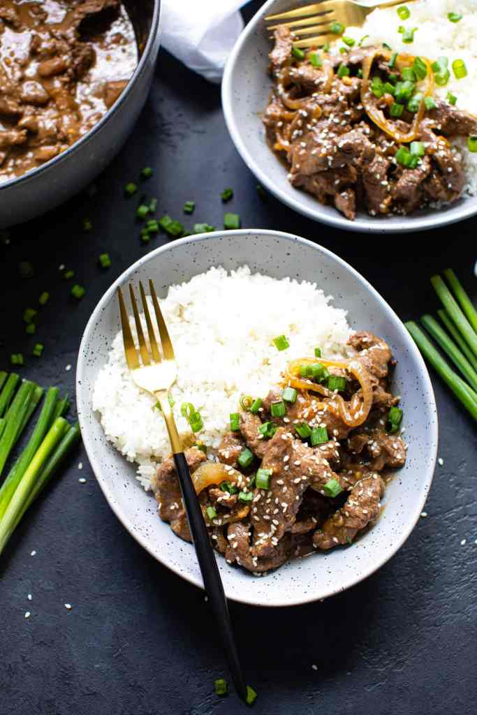two bowls of food on a black textured surface