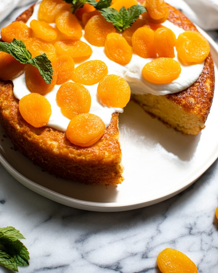 apricot cake on white plate on top of marbled counter