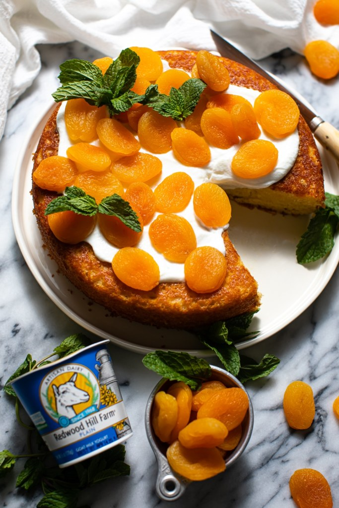 apricot snacking cake on white plate with mint garnish