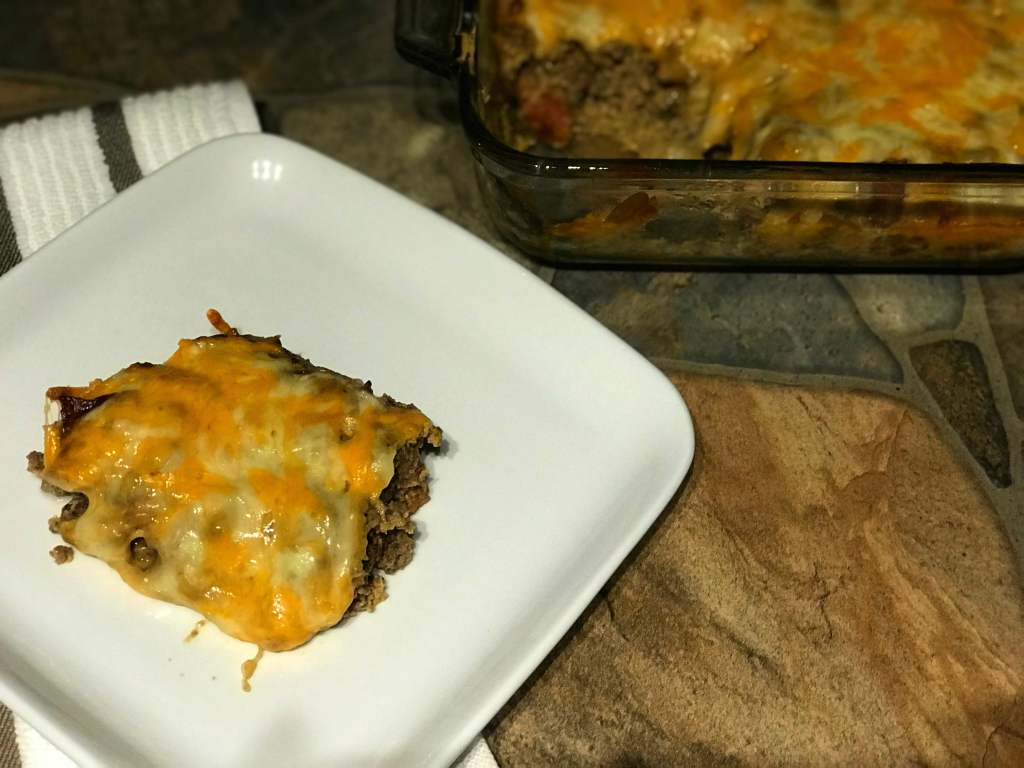 slice of cheeseburger casserole on plate next to the casserole dish