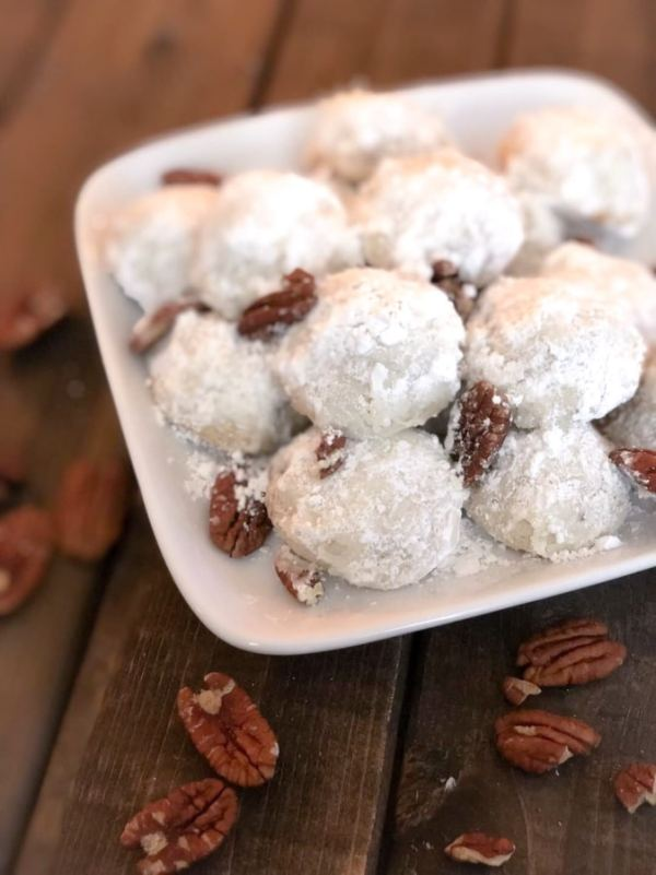 photo of snowball cookies on a platter and pecan scattered on the wooden table