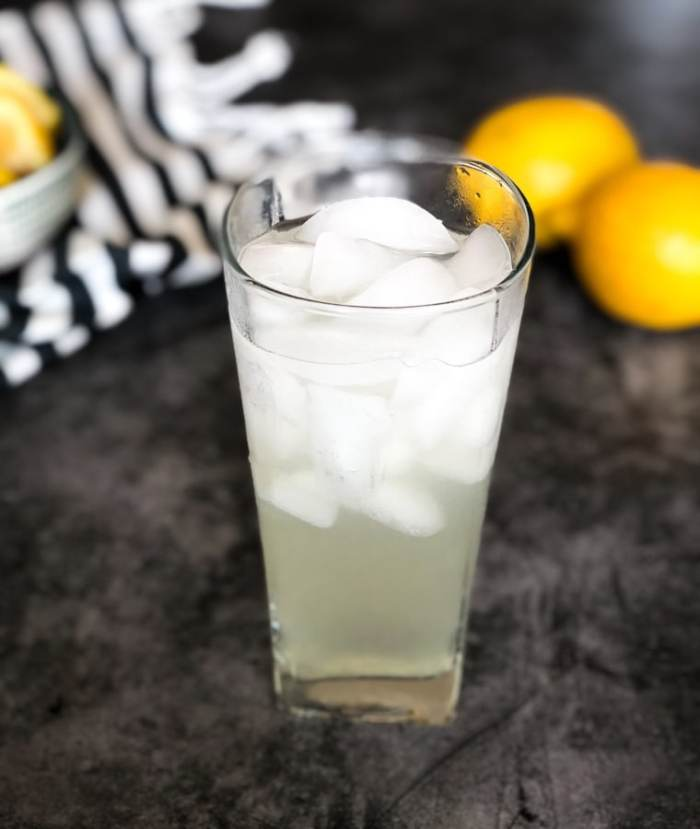 one tall glass of keto lemonade with lemons in the background
