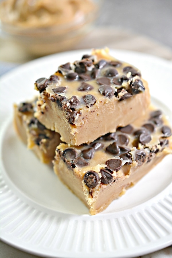 close up image of peanut butter fudge with two on the bottom and one piece of fudge stacked on top