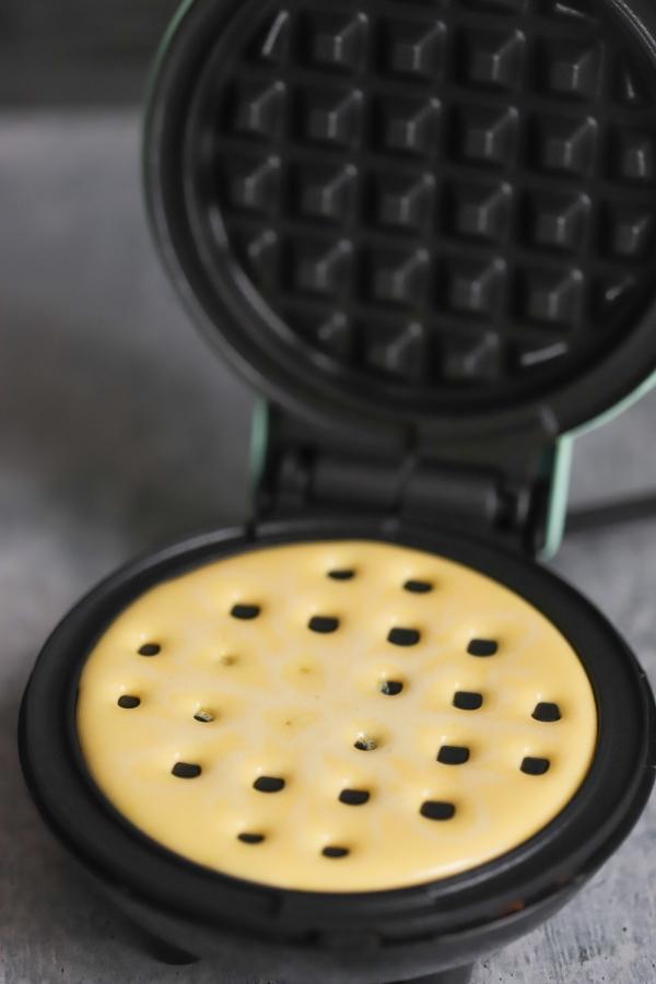 batter added to the waffle maker griddle