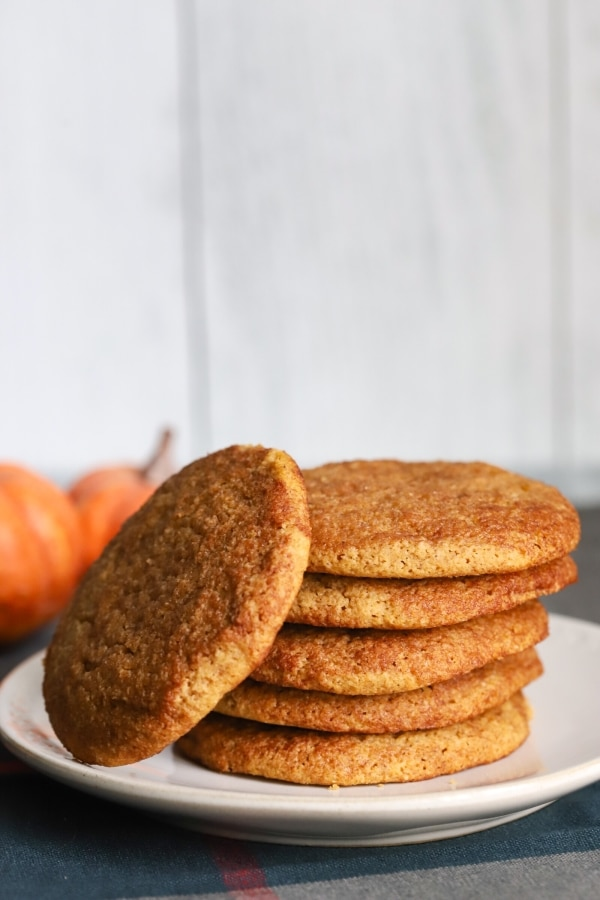 a stack of pumpkin snickerdoodle cookies with one slanted leaning next to the stack of cookies on a plate