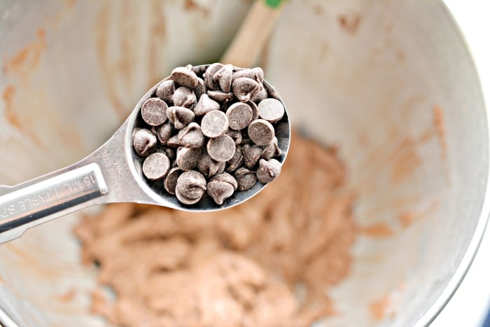spoon of sugar free chocolate chips over the mixing bowl
