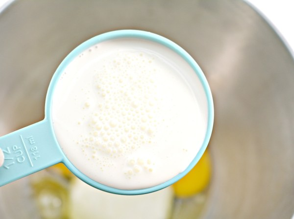 heavy cream in a measuring cup over a mixing bowl