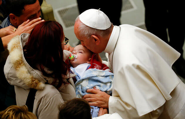 Pope Francis kisses a baby at the end of a special audience for Italy quake victims in Paul VI Hall at the Vatican January 5, 2017. REUTERS/Tony Gentile