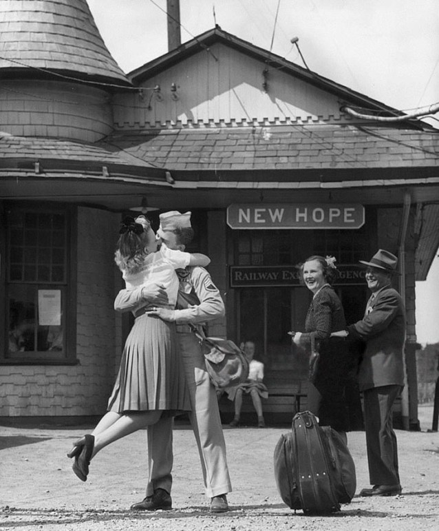 Wartime photos:A Young Woman Lifts Her Feet While Embracing And Kissing A Uniformed Us Soldier