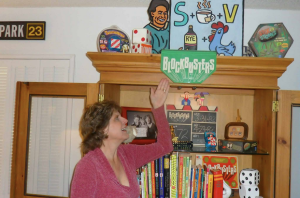 Cathi Ryan, Steve's wife, poses with some of his game show memorabilia, including the Blockbusters home game, logo from the front of Bill Cullen's podium, and the preserved slate from the final taping