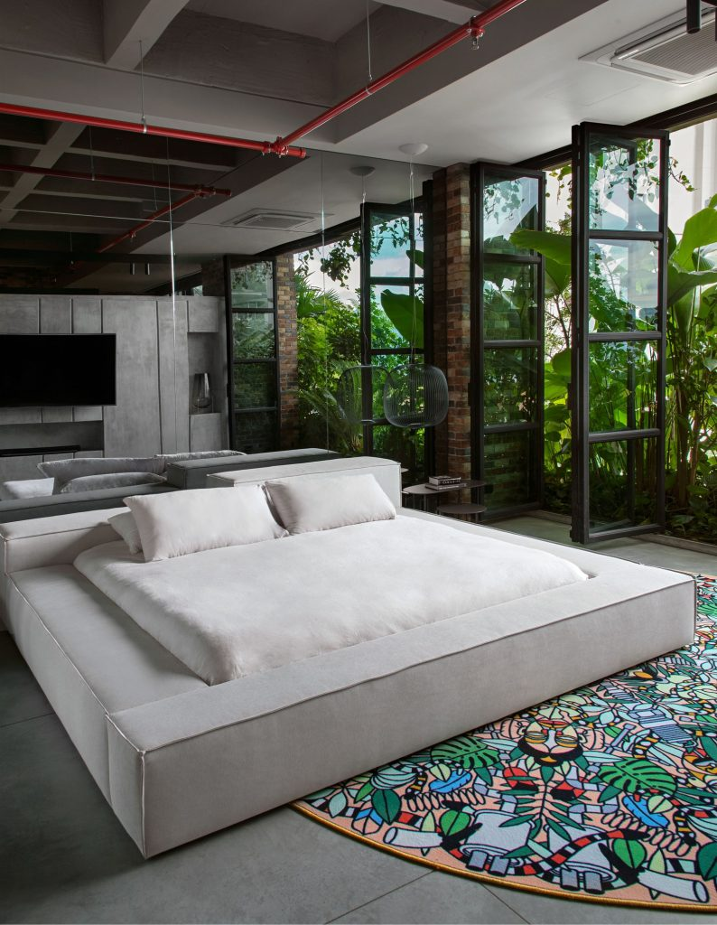 Loft bedroom with white bed frame and white bed linens. Includes a statement, nature inspired circle rug with large floor to ceiling windows to let in natural light. celebrity homes inspiration