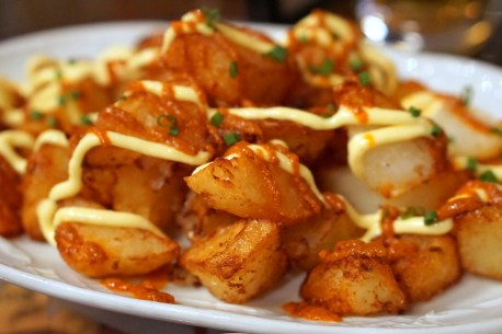 An easy spanish recipe: patatas bravas. Pictured here is the dish with sauce and mayonnaise drizzled on top, topped with fresh scallions