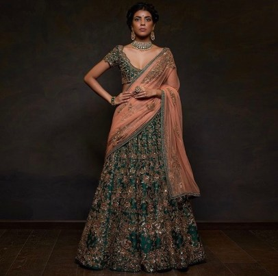 A stunning emerald green raw silk embroidered lehenga by Shyamal & Bhumika. Comes with a dusty pink tulle dupata.