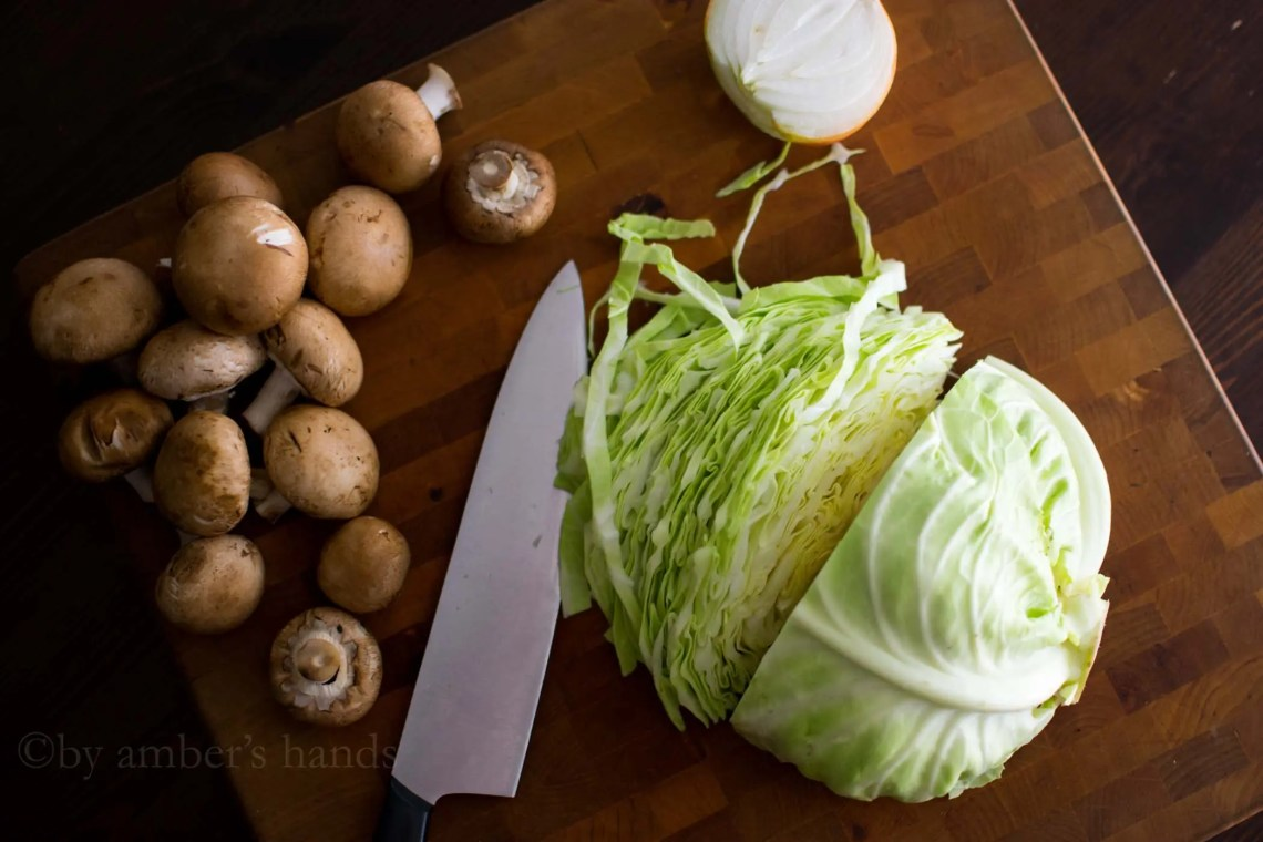 Chopping cabbage, mushrooms, and onion