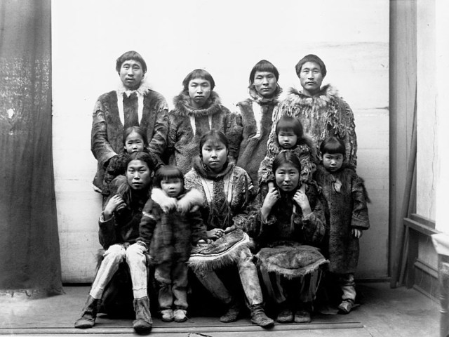 An Eskimo group of men, women, and children dressed in fur coats in Port Clarence, Alaska in 1894.