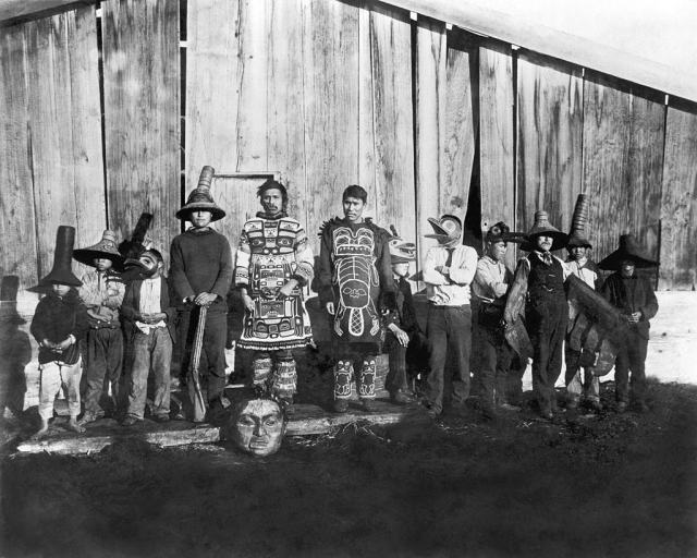 Indians in old dancing costumes in front of Chief Klart-Reech's house, Chilkat, Alaska, 1895.