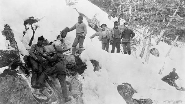 Eight men haul their eguipment up the snow covered Devil's Bluff near Sheep Camp, Alaska, 1895.