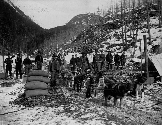 Prospectors pose with a dog sled team at an issolated camp in Yukon Territory near Dyea Canyon, Alaska, 1897.