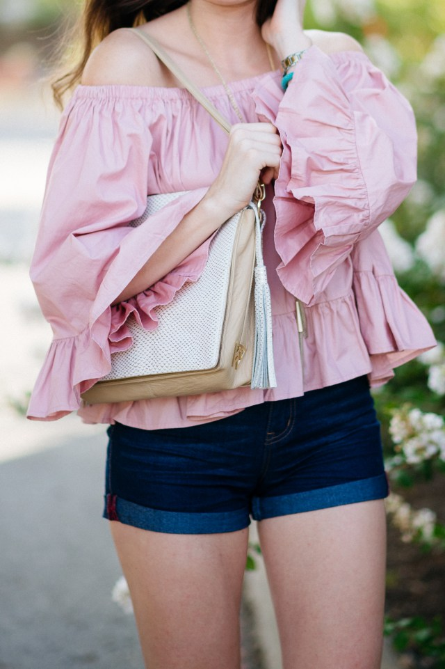 Wearing a pink ruffle blouse denim shorts kelly wynne bag