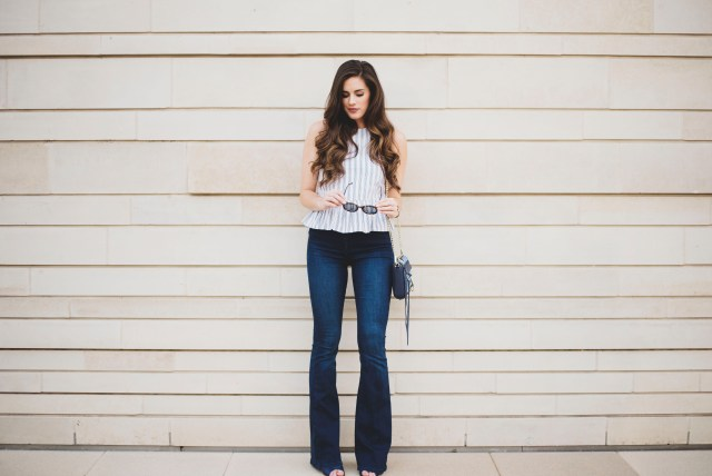 By, Hilary Rose in a peplum top, flare jeans, and patchwork bag