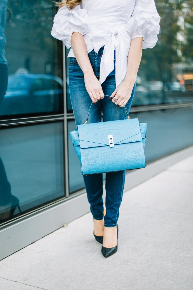 Hilary wearing a blue Henri Bendel bag with a chic wish wrap top in downtown Austin | By, Hilary Rose