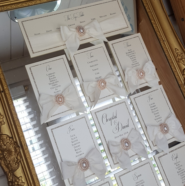 ivory and rose gold mirror table plan with silk bows and pearls