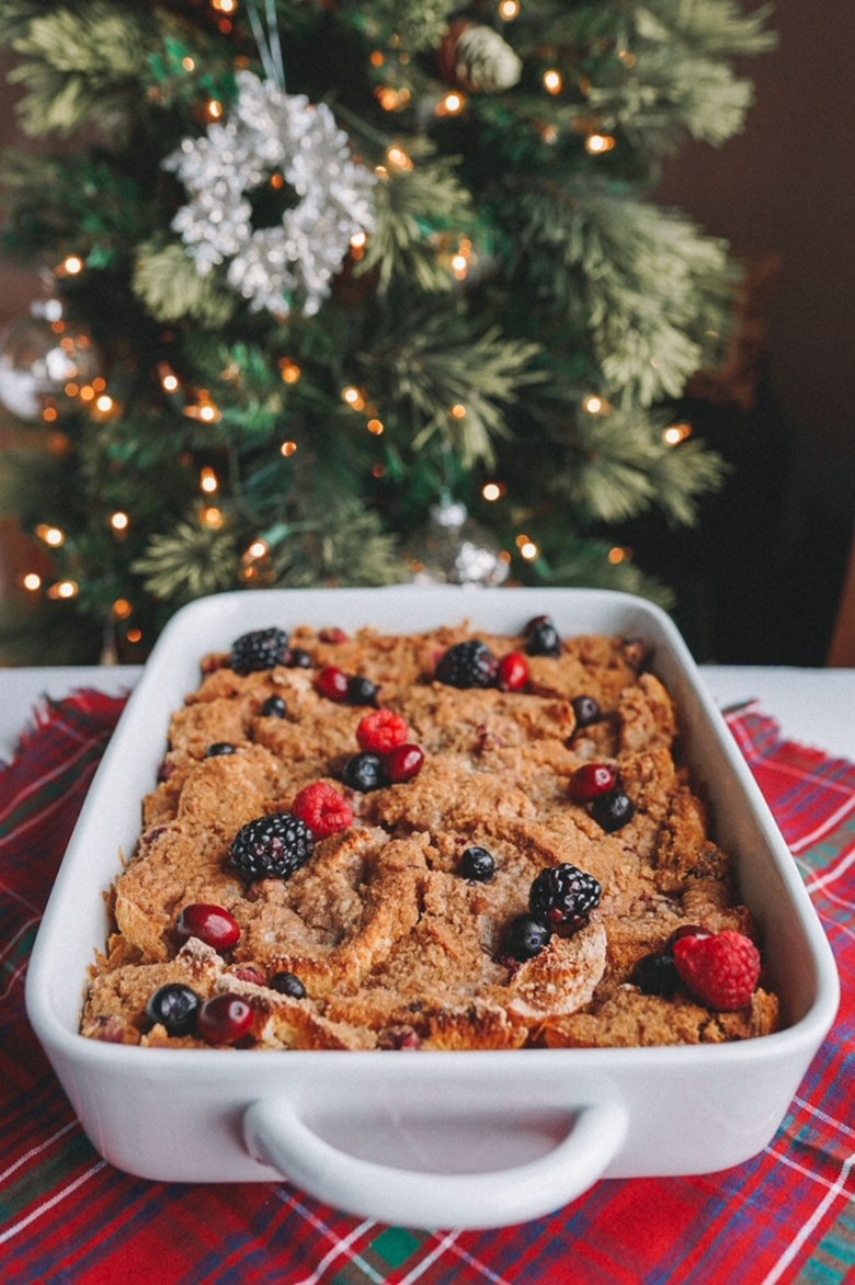 a slice of French toast bake with berries in white baking dish on red plaid napkin with Christmas tree in the background