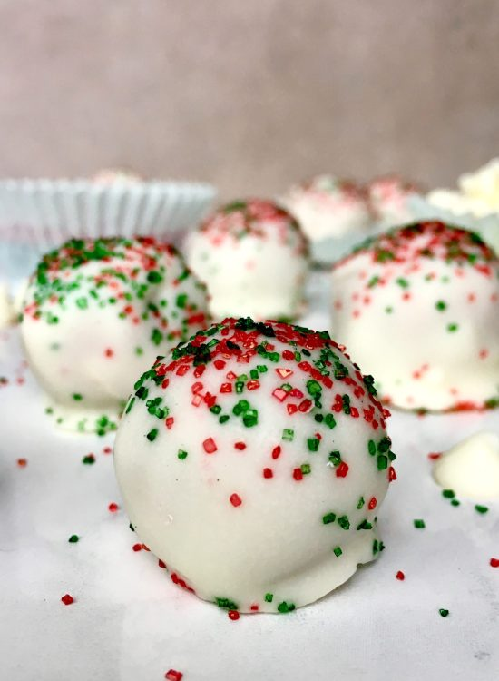 snickerdoodle cake balls with red and green sprinkles on white marble background