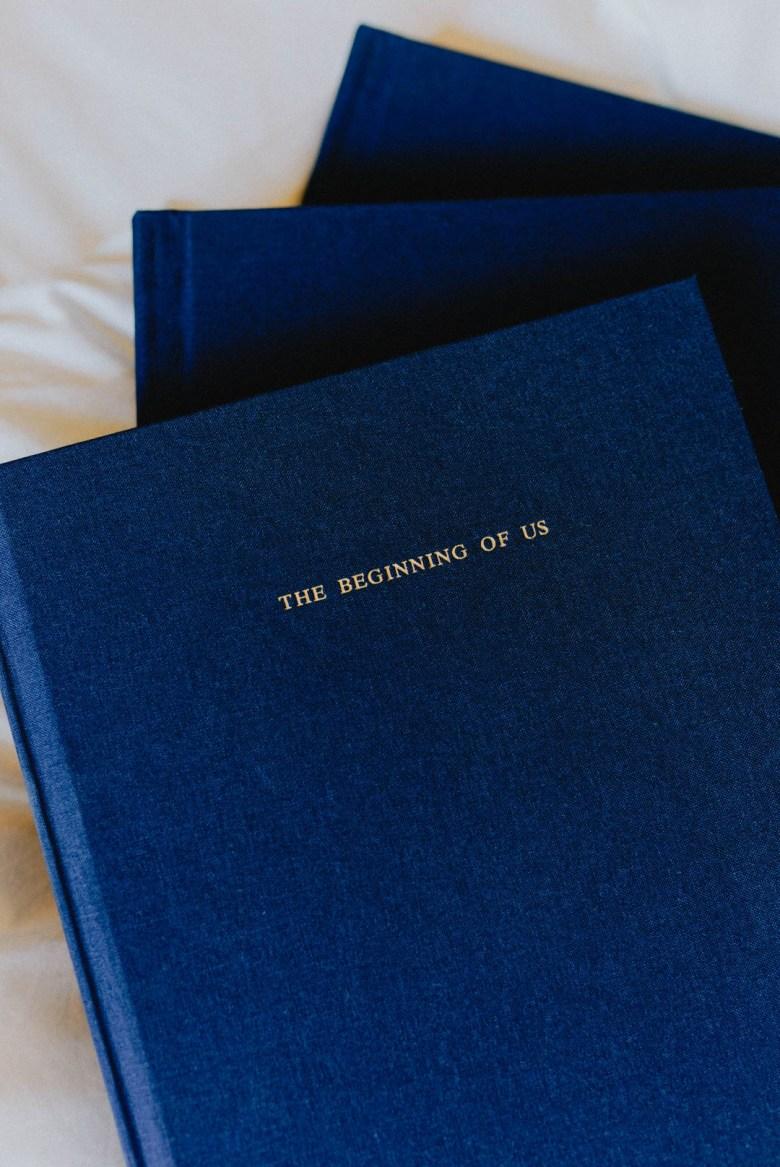 blue artifact uprising layflat photo albums on white bed