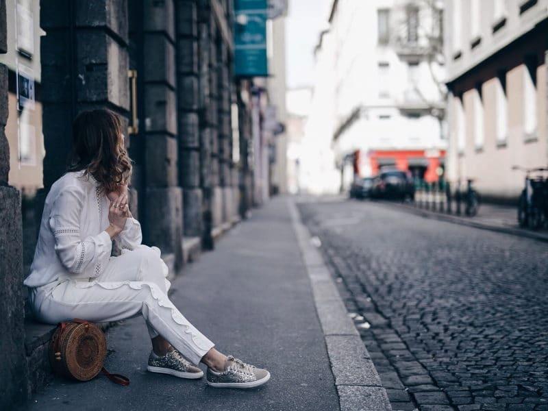 Look pantalon blanc à volants, blouse Navy Paris, sac rond Bali et baskets à paillettes assise
