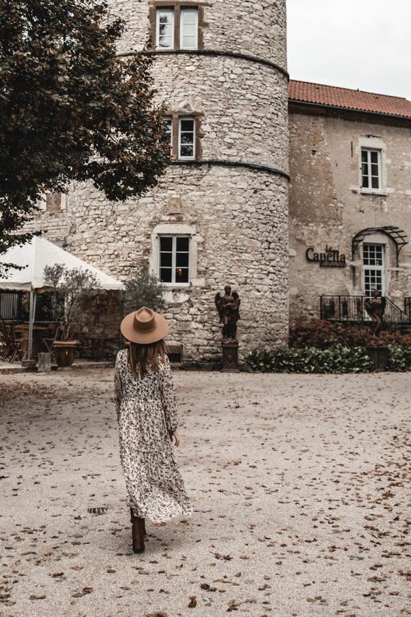 Un séjour ou un week-end au Château de Chapeau Cornu vers Lyon - Robe longue et chapeau devant la tour en pierres